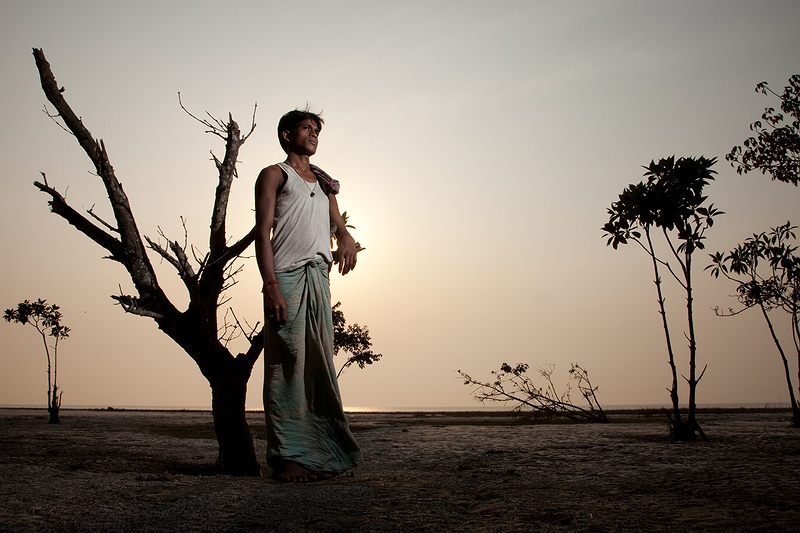 Farmer Simon Pradhan stands on the Hooghly River shore. Mangrove forests that have been planted to protect the island from increased tidal surges and cyclonic weather have been destroyed in many places. Rising sea level, subsidence, heavy storms and people logging for fire wood unaware that these forests are their best natural defence are the main reasons.